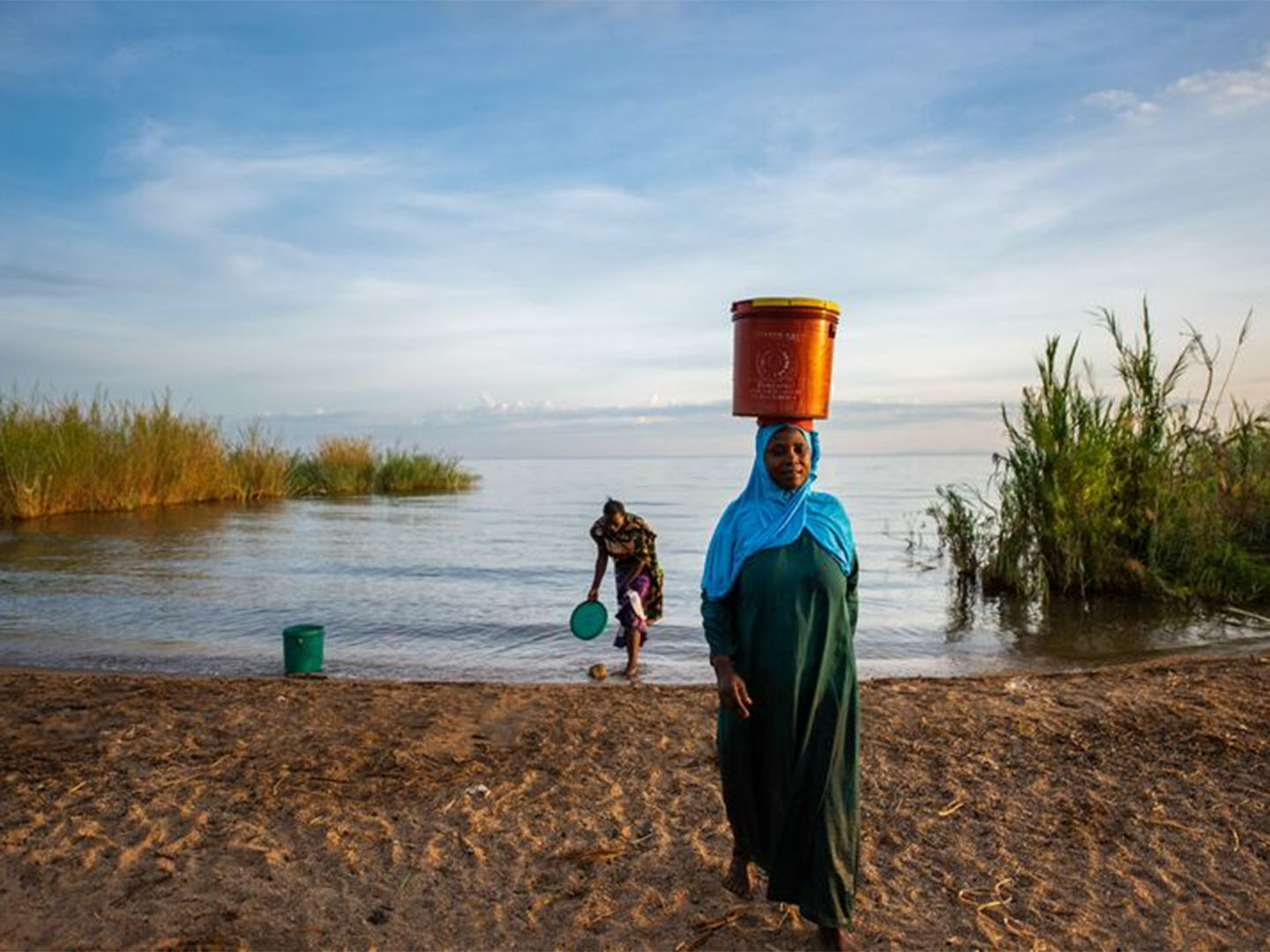 African woman carrying a bucket of water on her head. Photo courtesy of Roshni Lodhia/The Nature Conservancy.