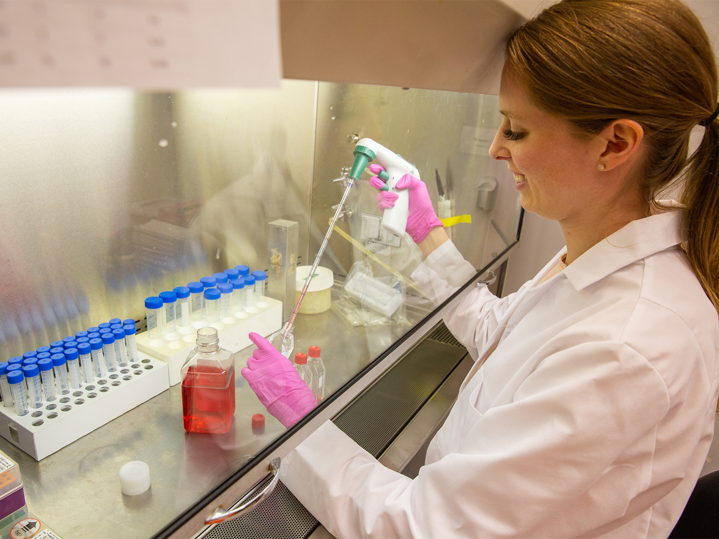 Researcher in a white coat pipetting in a lab