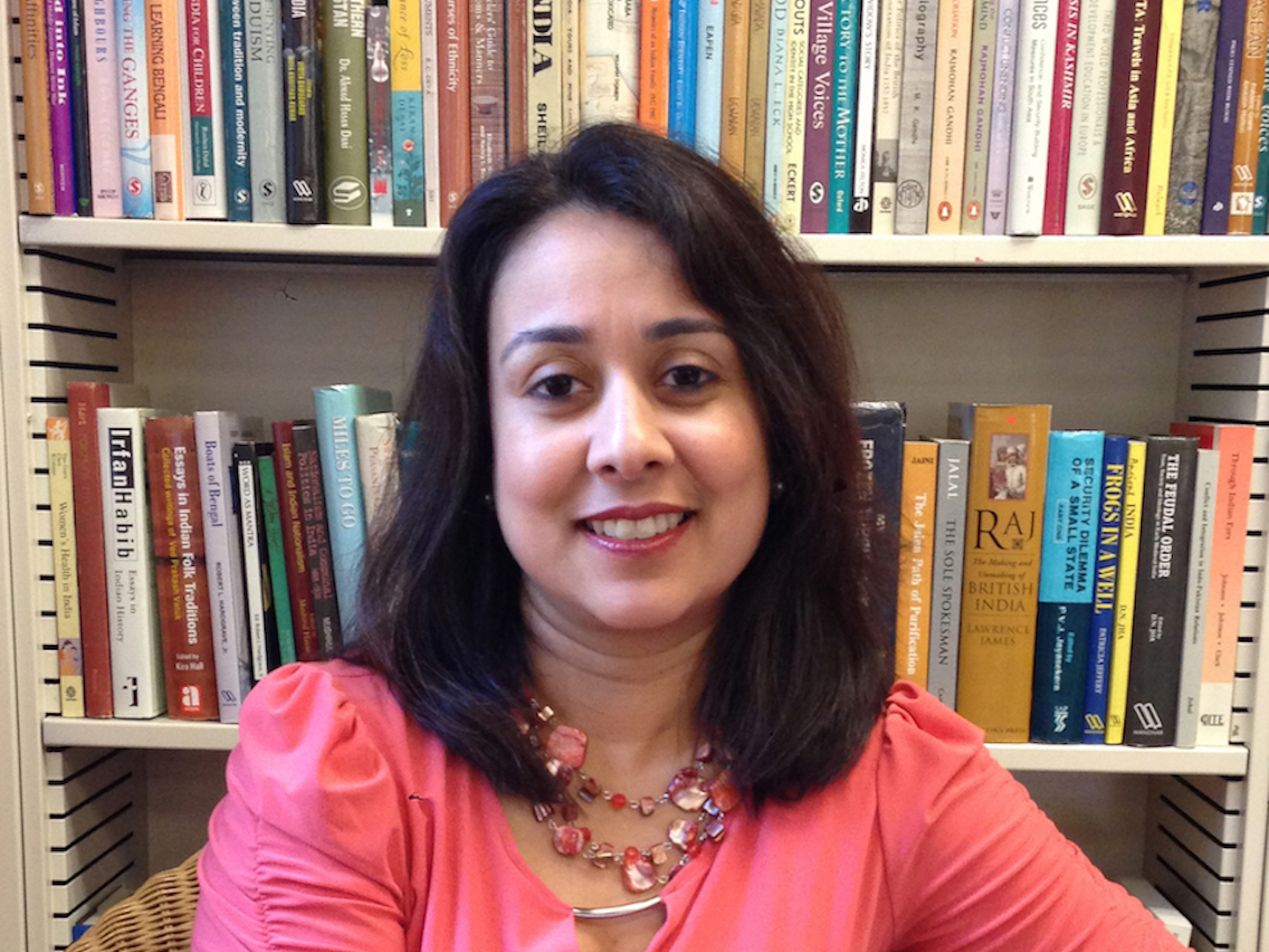 Sanchita Saxena seated in front of a bookcase