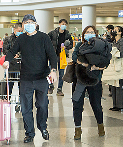 travelers wearing mask at airport