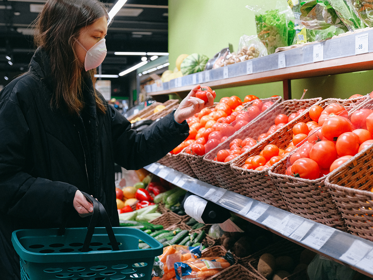 Young woman at supermarket wears protective mask during coronavirus