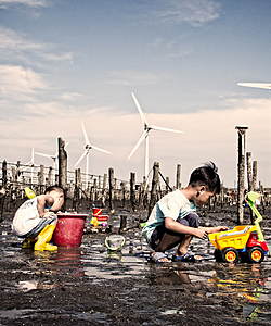 Two children play in the mud with windmills in the background.