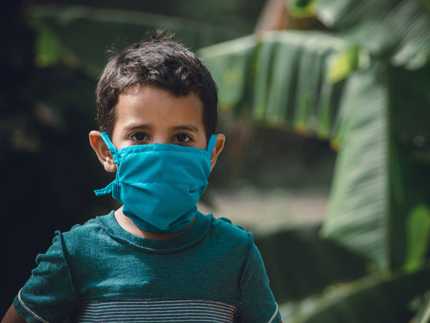 Boy in blue mask and green shirt in front of tropical leaves