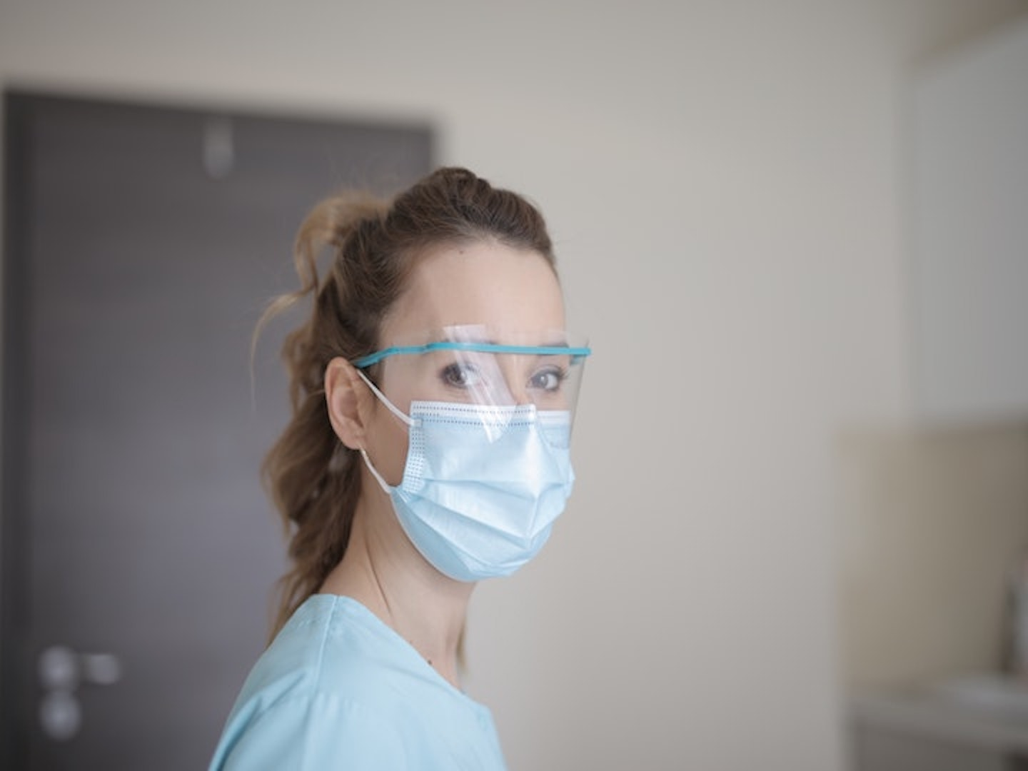 This is a woman wearing in blue shirt, face mask and a pair of protective glasses.