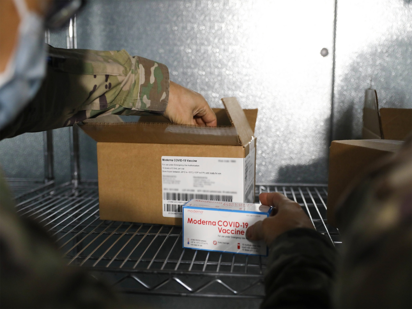 Soldier's hand reaching into box containing COVID-19 Moderna vaccine boxes (U.S. Army photo by Spc. Erin Conway)