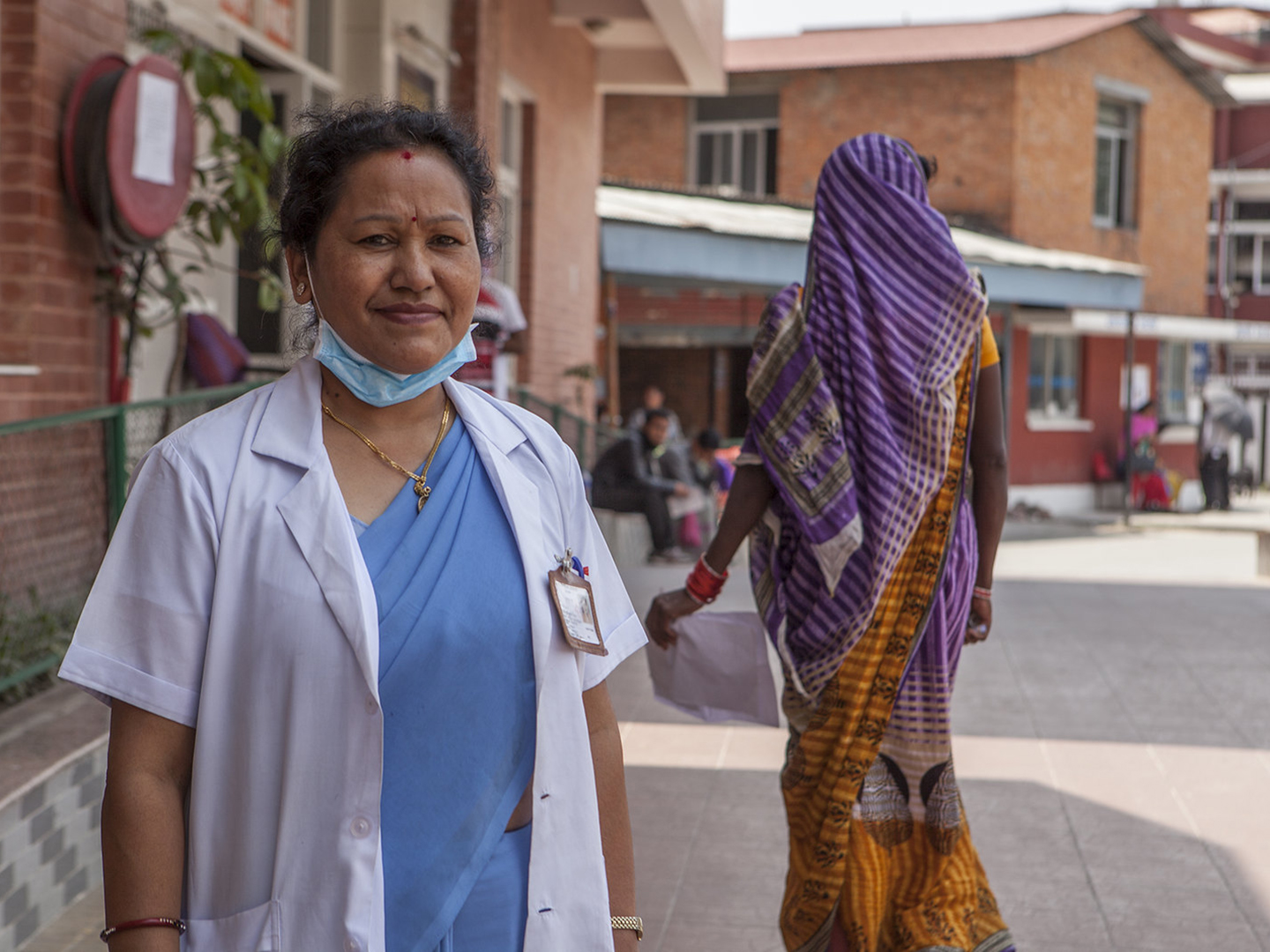 USAID nursing director smiling with mask below her face and a woman walking behind her (Kashish Das Shrestha for USAID)
