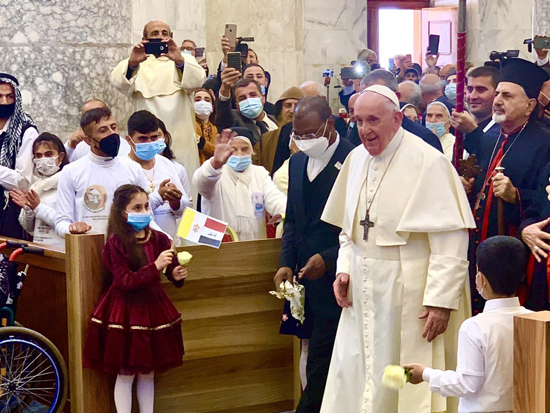 Pope Francis walks down the aisle of an Iraqi church