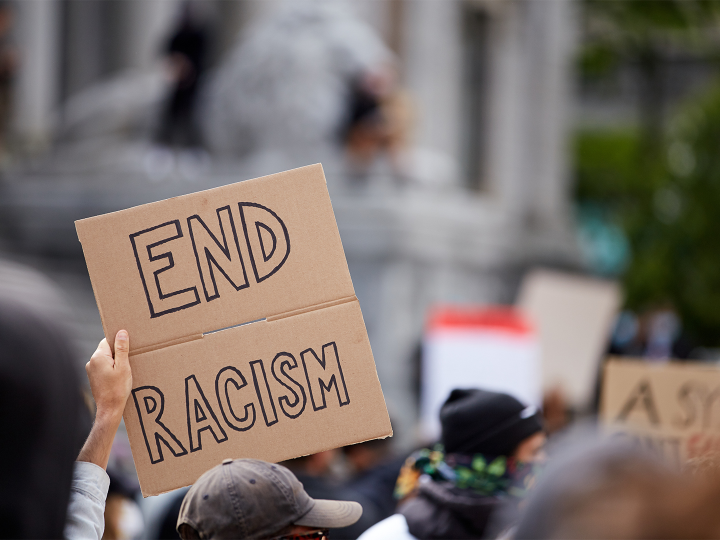 """Protestor holding poster that reads """"end racism""""."""