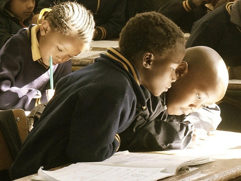Black elementary school students study at their desks