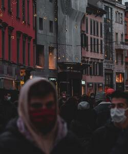 A crowd of people in a city wearing masks to prevent the spread of COVID-19
