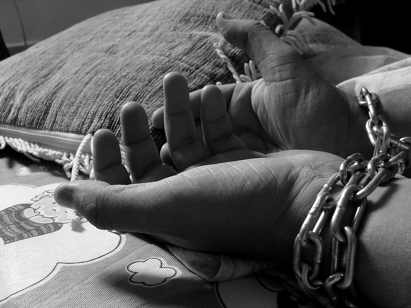 Black and white photo of hands in chains on top of a children's blanket