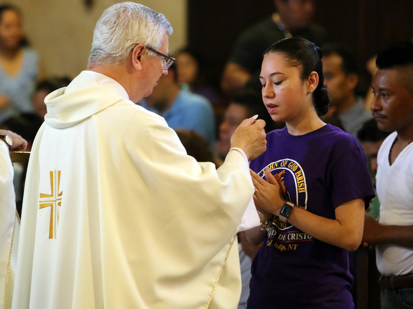 Young Latina woman receives communion