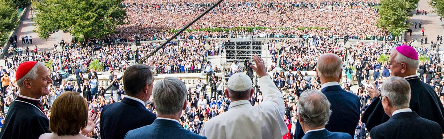 Pope Francis waves at a crowd of people gathered.