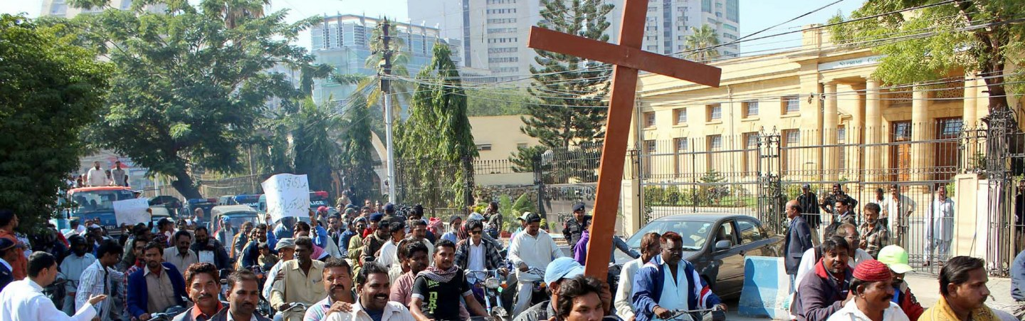 A group of people carrying a cross in a street.