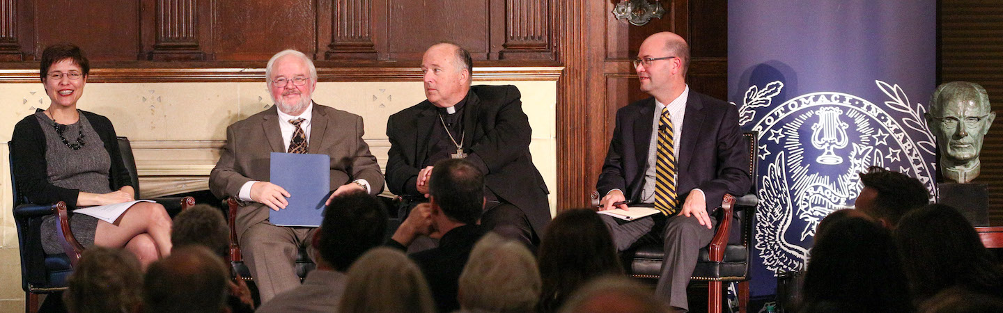 The panelists discuss the legacy of John Courtney Murray with a bust of him to the right of the image.