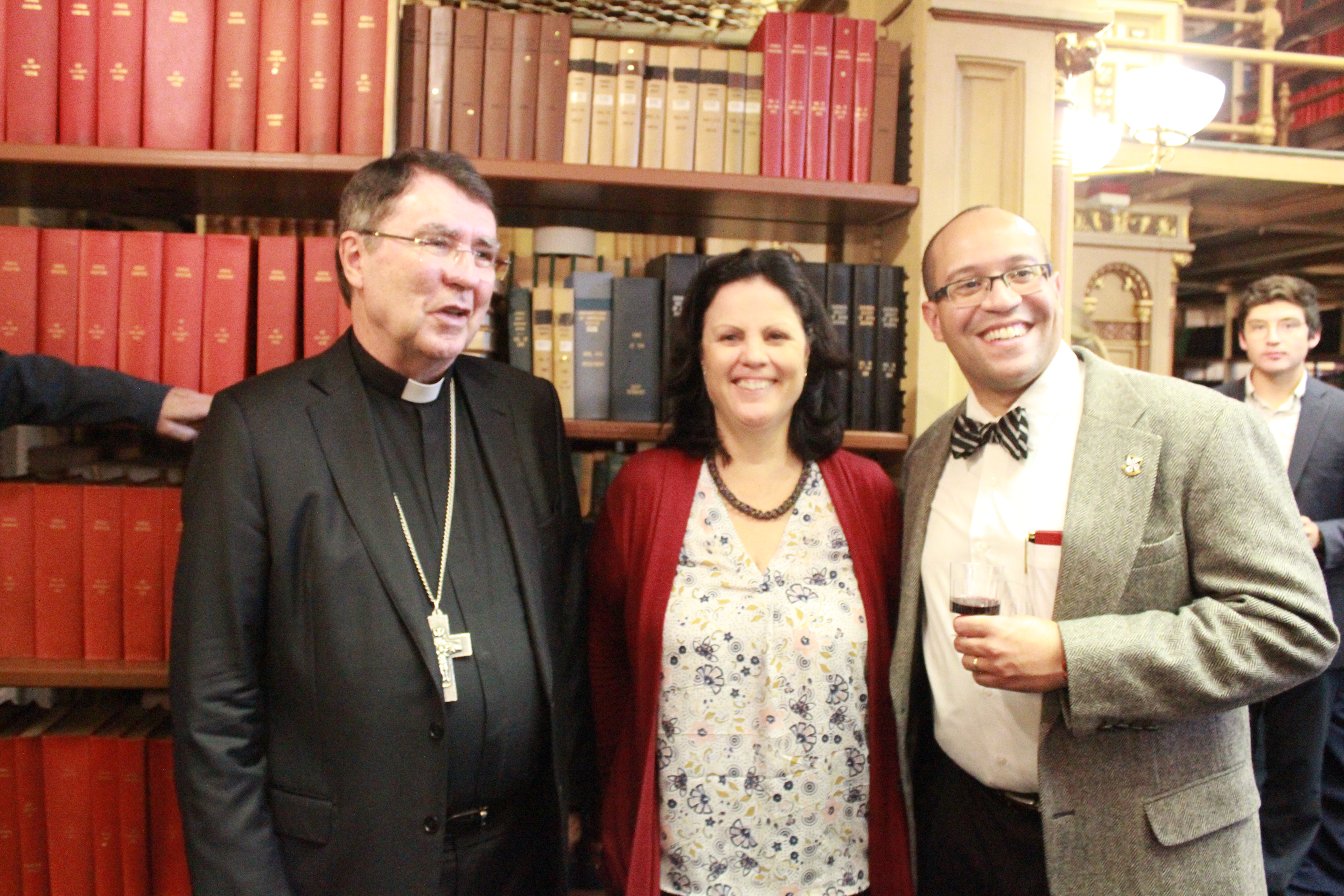 Two participants smile as they meet Archbishop Pierre in Riggs Library following the event.