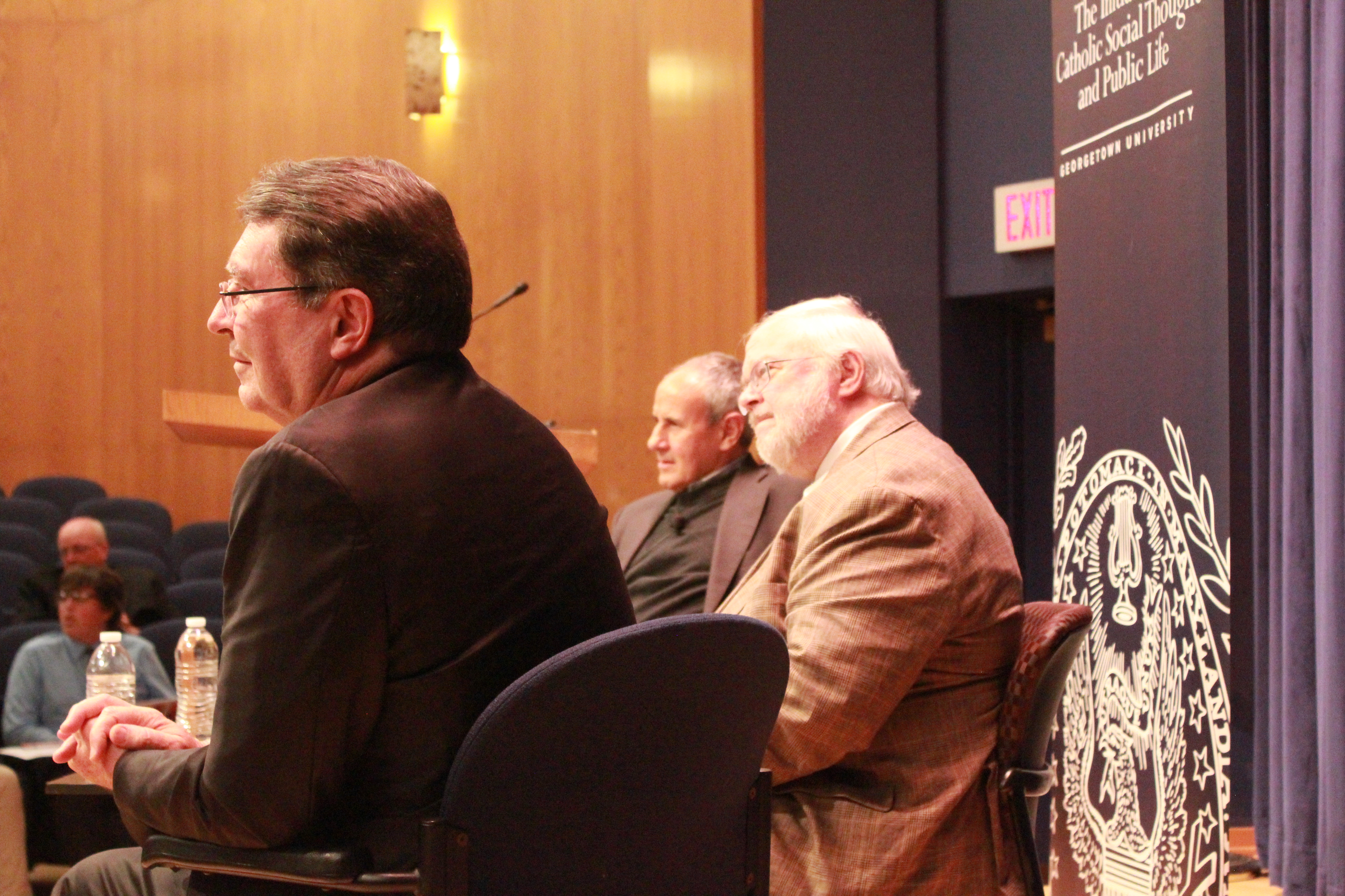 The panel leans in as a member of the audience asks a question exploring the messages of the discussion in more depth.