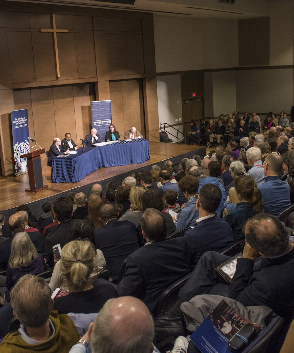 The panelists speak to a packed Trinity Hall.