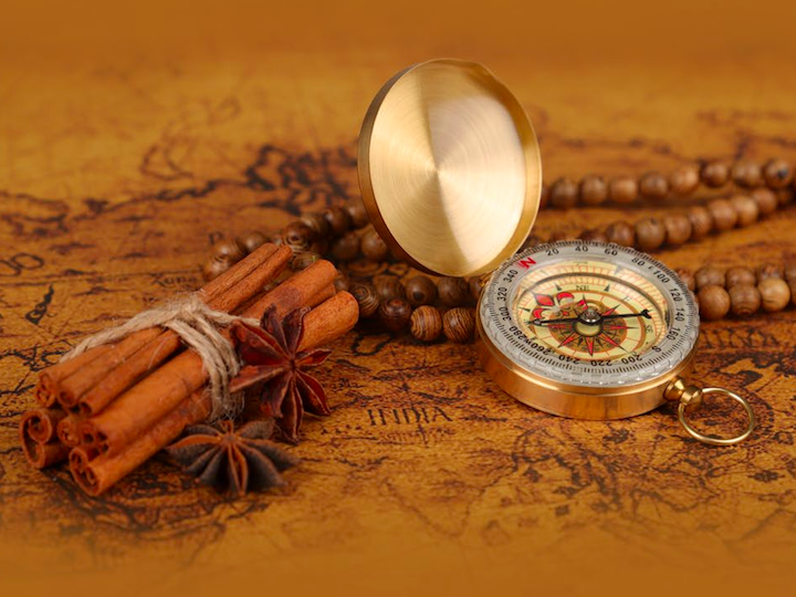 Cinnamon, compass, and beads on an old map.