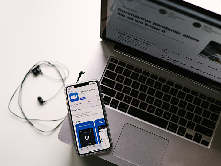 An iPhone open to the Zoom app sits on top of a laptop with an article about the impact of the COVID-19 pandemic