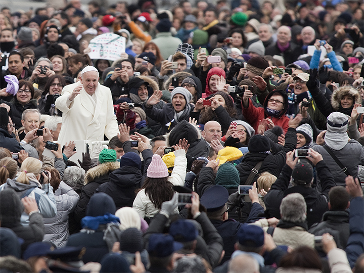 Pope Francis waving to a large crowd of people