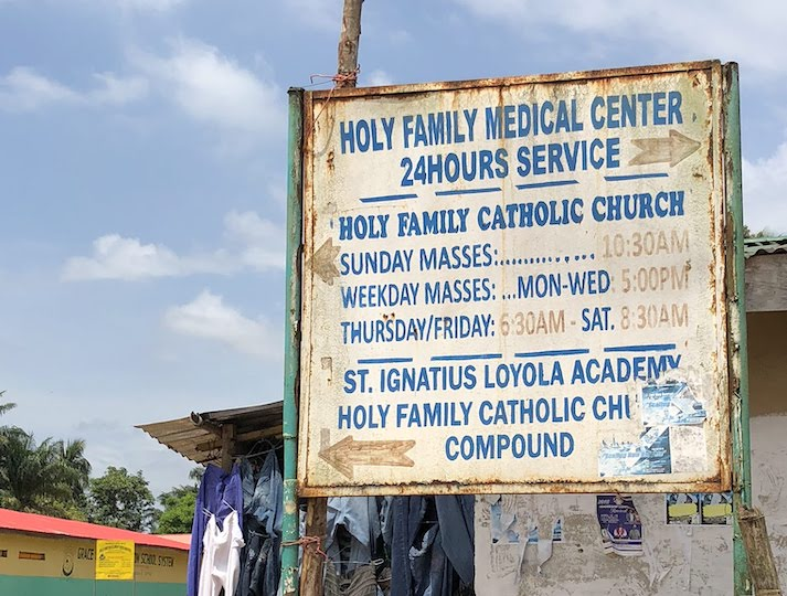 A sign displaying hours of operation for the Holy Family Medical Center and Church in Caldwell, Liberia