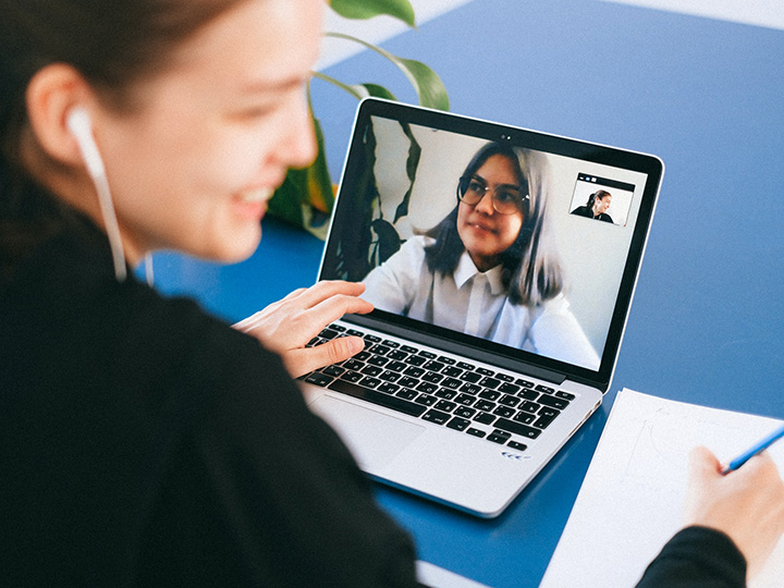 Woman smiling while on a video call on a laptop