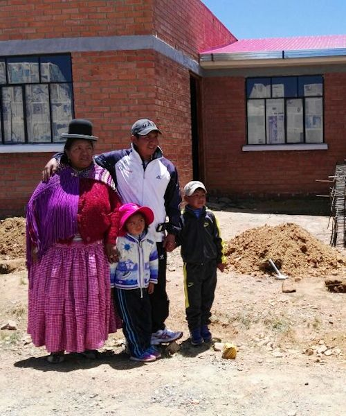 Fuller Center for Housing Bolivia beneficiaries stand with their new home