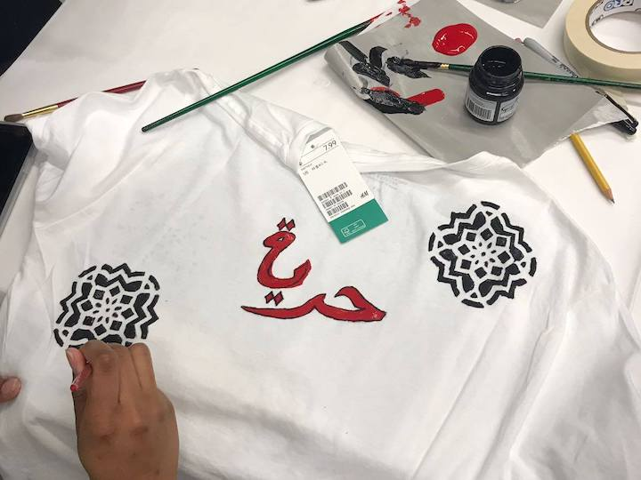 A member of Arab Society decorates a shirt during the club's calligraphy workshop