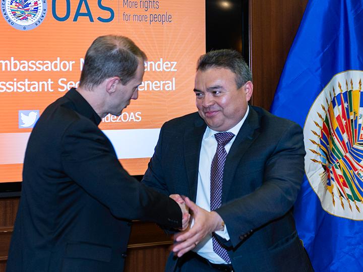 Father Matthew Carnes and Ambassador Nestor Mendez shake hands
