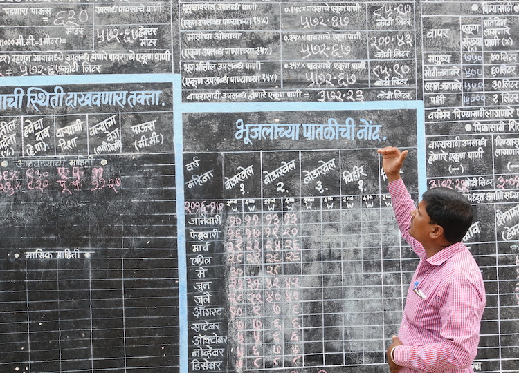 A villager in rural Ahmednagar explains a hydrological table that calculates per capita water usage and tracks monsoon rainfall