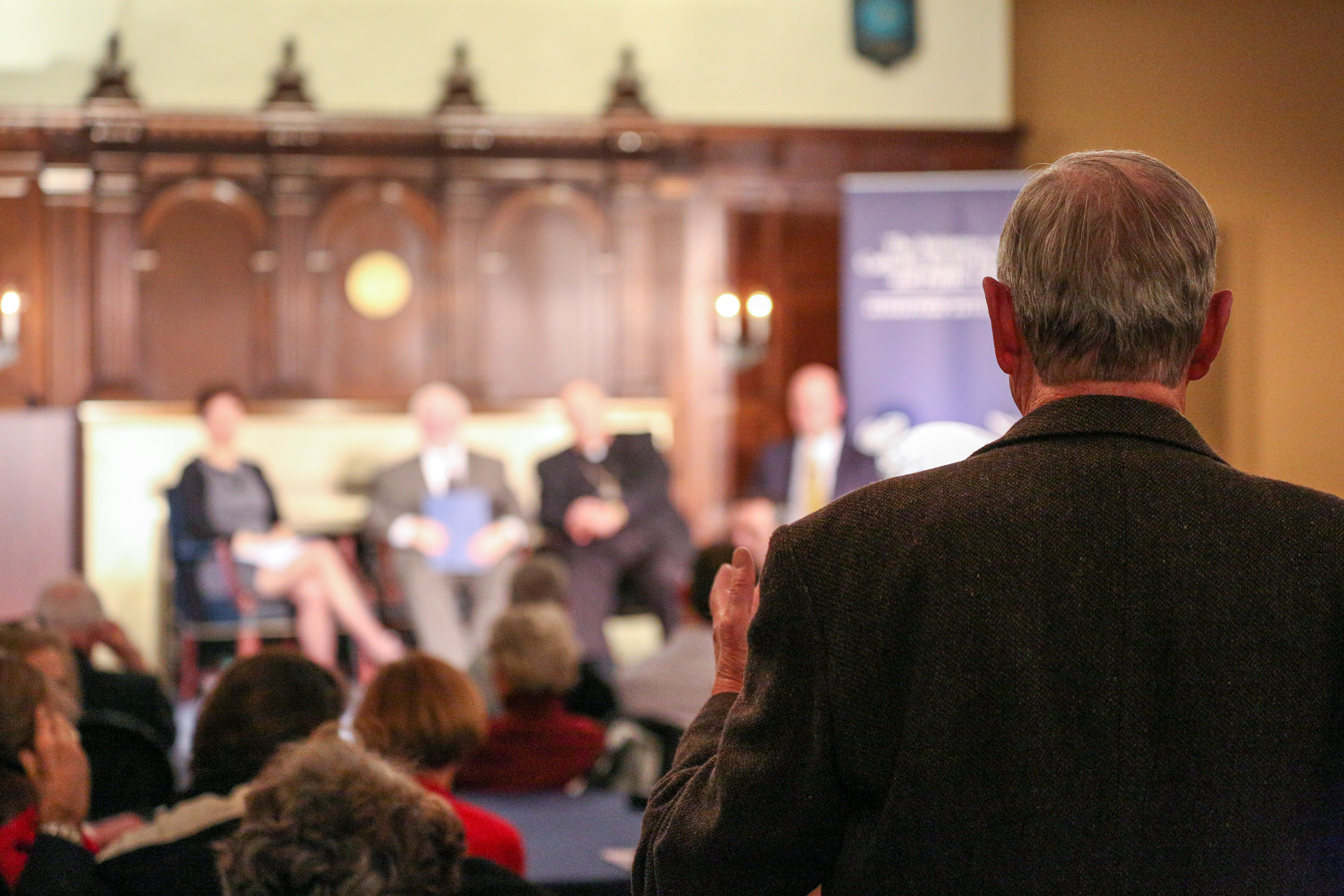 A member of the audience asks a question of the panel.