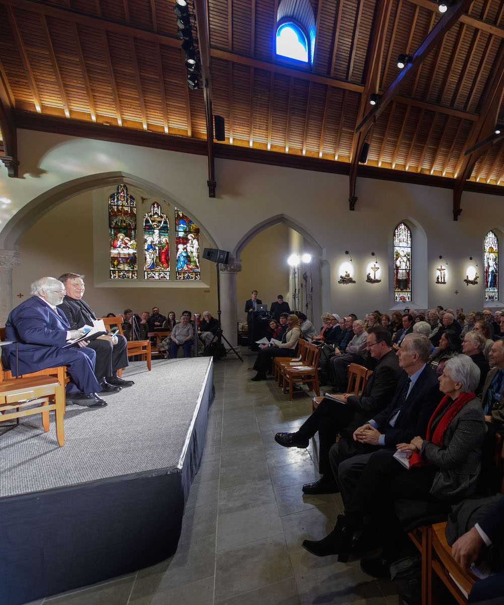 CST Director John Carr and Cardinal Tobin in front of a crowded Dahlgren Chapel pews.