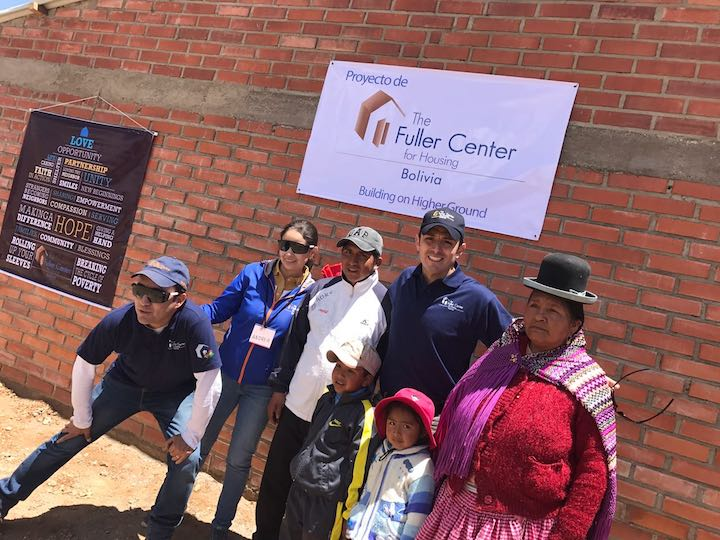 Fuller Center for Housing Bolivia staff, including Carlos Aramayo, stand with the beneficiary family