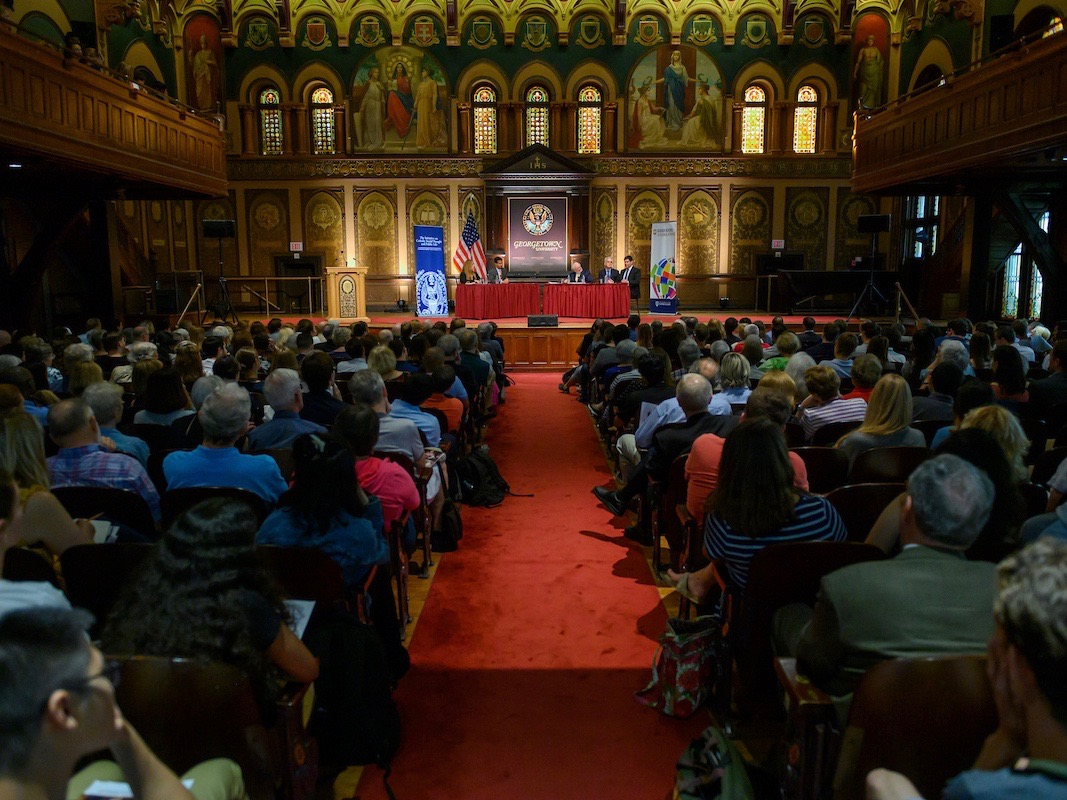 "A full house in historic Gaston Hall for the Public Dialogue on ""The U.S. Response to the Global Migration Crisis."""