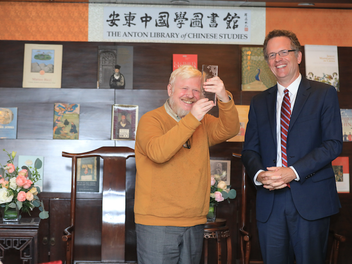 Benoit Vermander, S.J., Fudan University, happily accepts his gift from GU Vice President for Global Engagement and event moderator Thomas Banchoff.