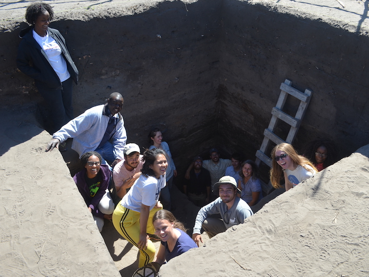 Students and researchers stand in excavation site.