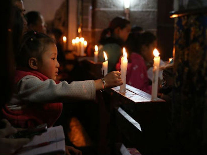 An Asian child lights a candle in church