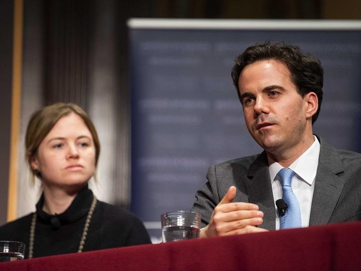 Panelist Robert Costa speaks with panelist Elizabeth Dias in the background