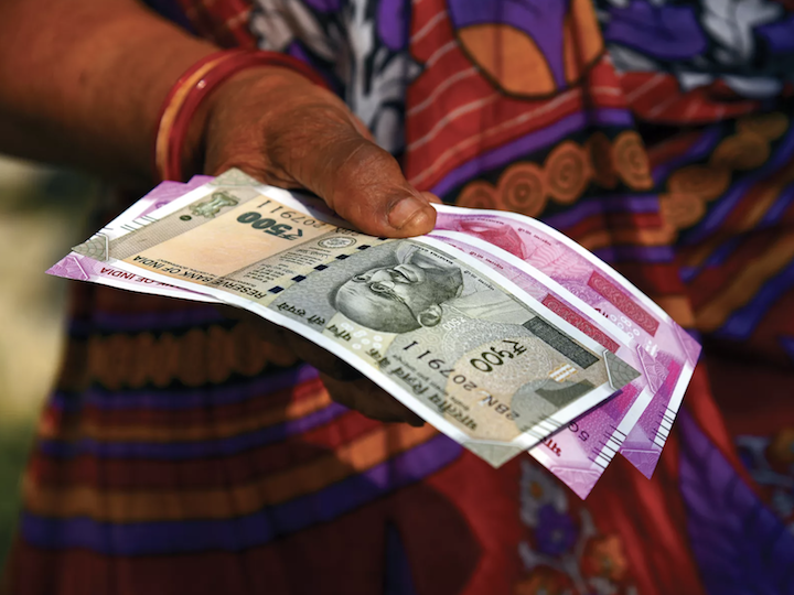 A woman in India holding rupees.