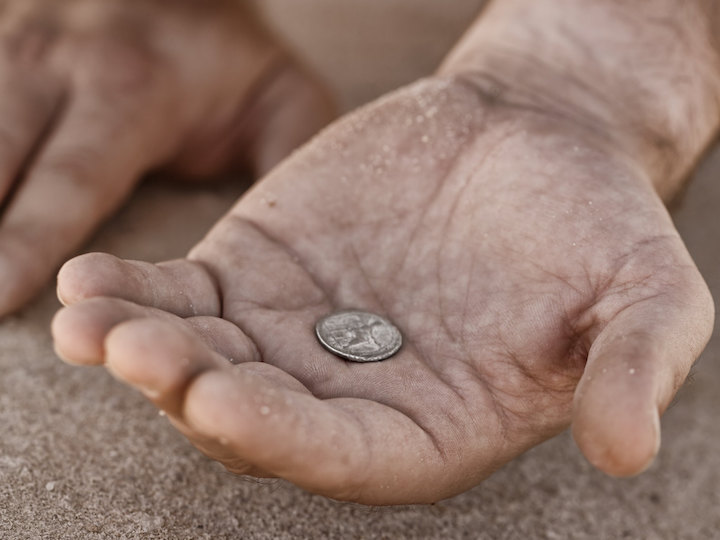 Coin in the hand of a beggar
