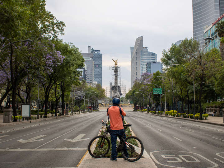A panoramic of an empty Paseo de la Reforma in Mexico City and a person in a bike