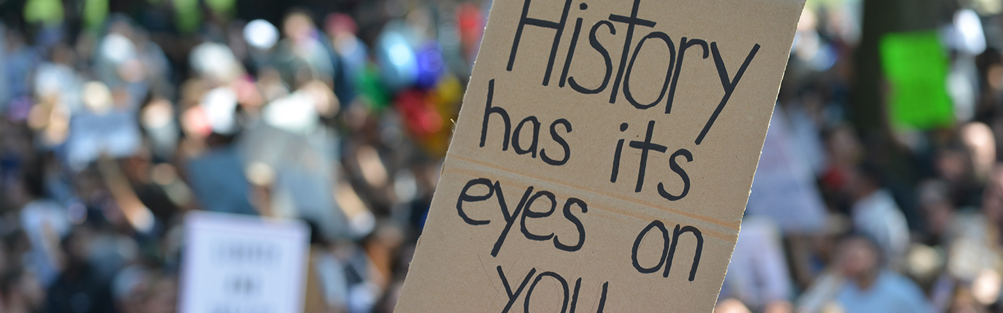 """a person holding a sign with """"history has its eyes on you"""" on it"""
