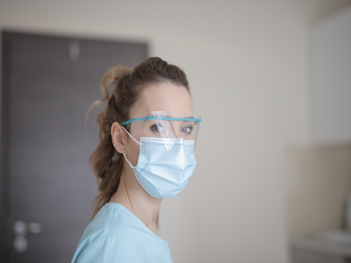 This is a picture of a female caregiver in blue shirt. She wears a mask and a pair of protection glasses.