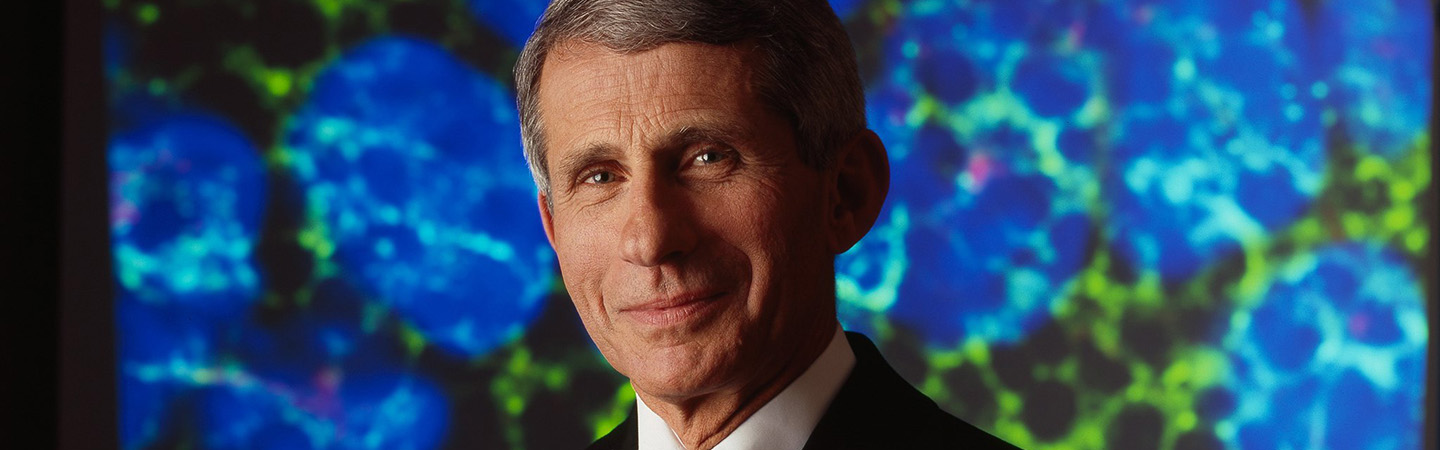This is a picture of Dr. Fauci. The background is blue. He is wearing a black suit.