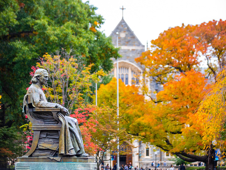 John Carroll statue in front of tree changing colors