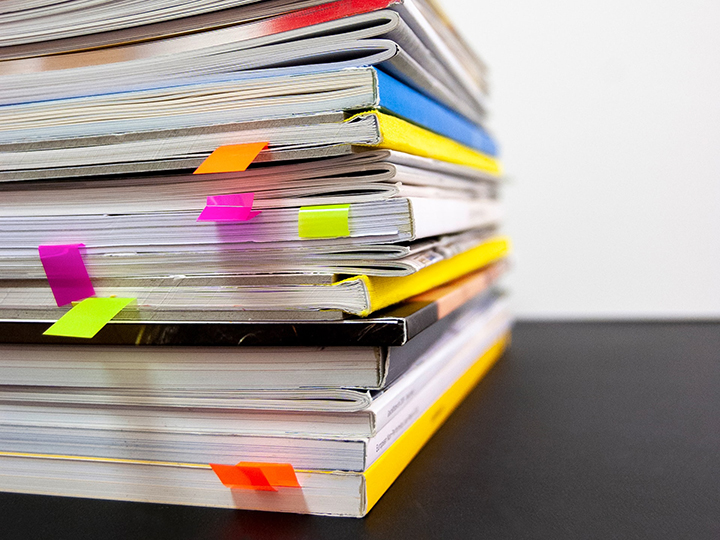 Stack of colorful notebooks with sticky note flags
