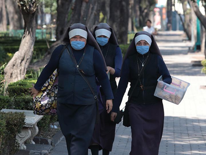 Nuns wearing masks walking on the sidewalk in Mexico