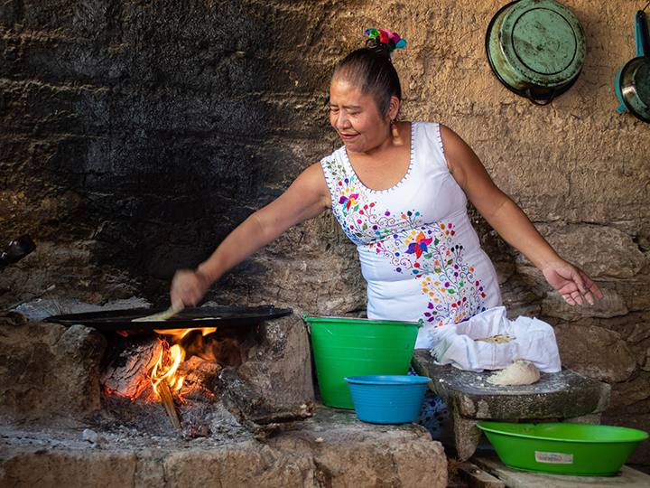 Woman cooking tortillas over a wood oven