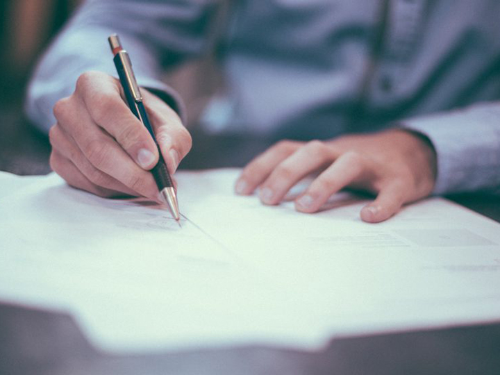 Man writing with pen and paper